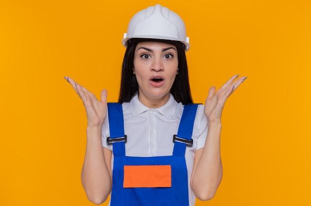 Mulher jovem construtora em uniforme de construção e capacete de segurança olhando para a frente feliz e surpresa, levantando os braços em pé sobre a parede laranja