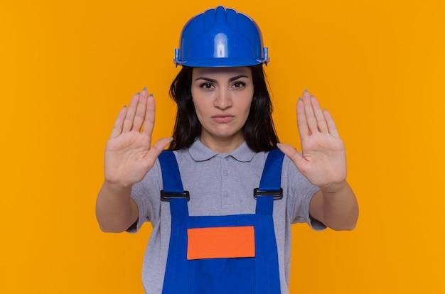 Mulher jovem construtora em uniforme de construção e capacete de segurança olhando para frente com uma cara séria, fazendo gesto de parada com as mãos em pé sobre a parede laranja