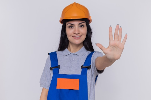 Mulher jovem construtora em uniforme de construção e capacete de segurança olhando para frente sorrindo confiante, fazendo gesto de parada com a mão aberta em pé sobre a parede branca