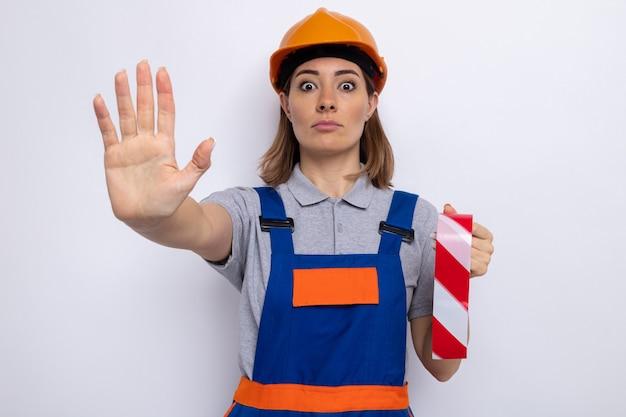 Mulher jovem construtora em uniforme de construção e capacete de segurança segurando fita adesiva preocupada em fazer gesto de parada com a mão em pé sobre a parede branca