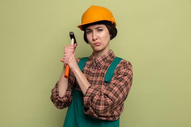 Mulher jovem construtora em uniforme de construção e capacete de segurança segurando um martelo com cara séria em pé no verde