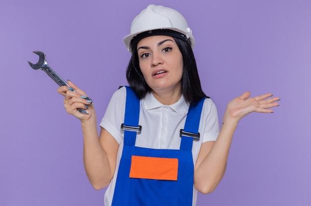 Mulher jovem construtora em uniforme de construção e capacete de segurança segurando uma chave inglesa, olhando para a frente, confusa, levantando os braços, sem resposta em pé sobre a parede roxa