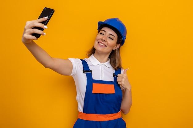 Mulher jovem construtora em uniforme de construção e capacete de segurança sorrindo alegremente feliz e positiva fazendo selfie usando smartphone mostrando os polegares em pé sobre a parede laranja