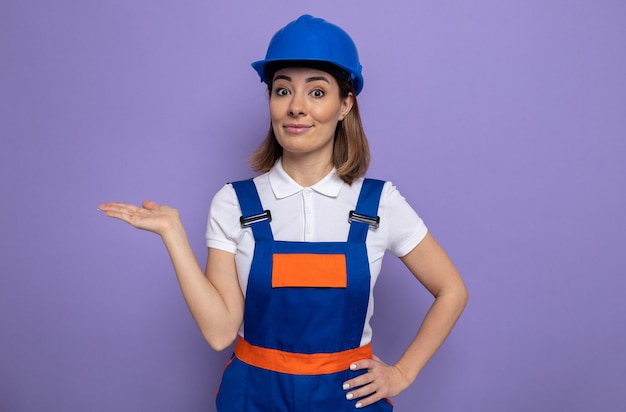 Mulher jovem construtora feliz em uniforme de construção e capacete de segurança, olhando para a frente, sorrindo confiante, apresentando o espaço da cópia com o braço da mão em pé sobre a parede roxa