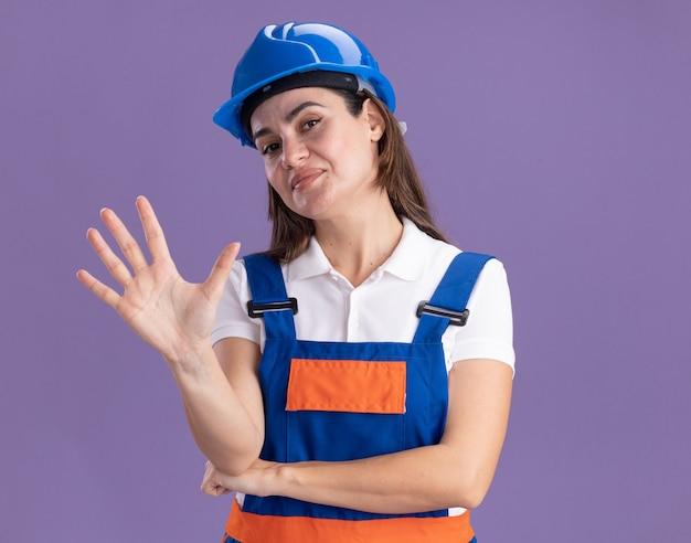 Mulher jovem construtora satisfeita de uniforme, mostrando cinco isolados na parede roxa