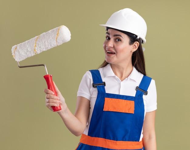 Mulher jovem construtora satisfeita de uniforme segurando a escova giratória isolada na parede verde oliva