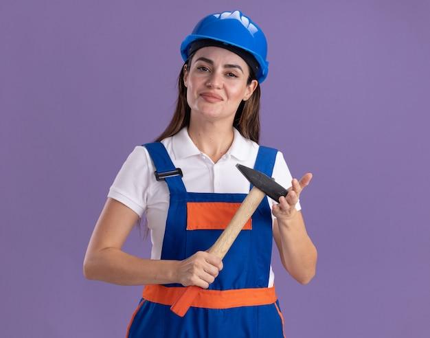Mulher jovem construtora satisfeita de uniforme segurando um martelo isolado na parede roxa