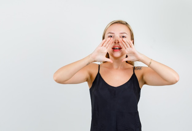 Mulher jovem contando um segredo em camiseta preta