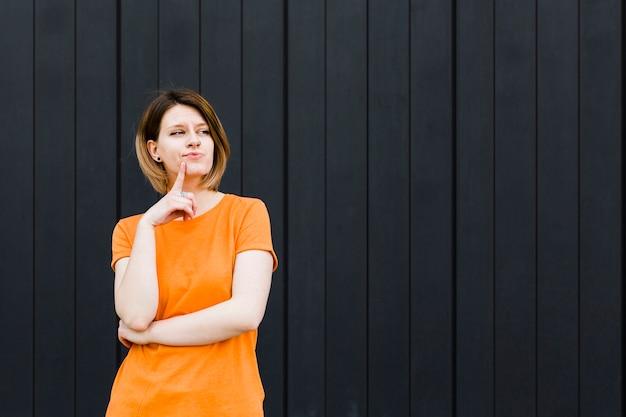 Mulher jovem contemplada com o dedo no queixo contra parede preta
