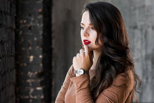 Mulher jovem contemplada com relógio de pulso na mão olhando para longe