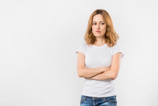 Mulher jovem contemplada franzindo os lábios em pé com os braços cruzados contra o pano de fundo branco