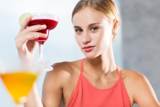 Mulher jovem conteúdo de vidro levantamento de cocktail