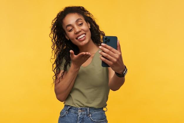 Mulher jovem conversa por vídeo com o namorado, sorri amplamente e se sente feliz e satisfeita, manda beijo no ar