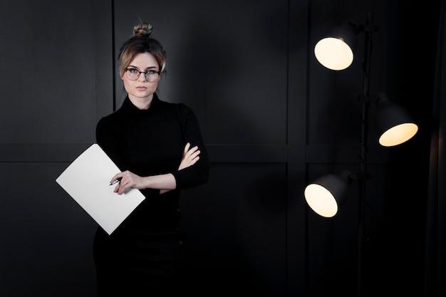 Mulher jovem corporativa com óculos segurando papéis