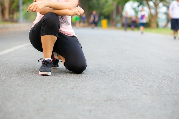 Mulher jovem corredor descansando na estrada.
