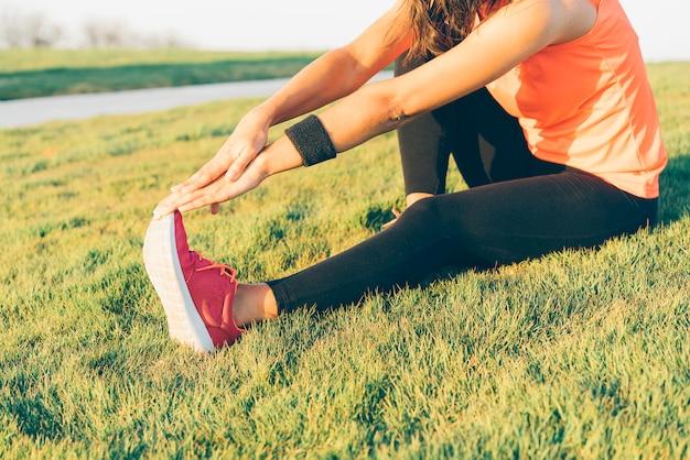 Mulher jovem corredor esticando as pernas antes de executar em um parque. feche acima da menina atlética e saudável que veste as sapatilhas brancas e cor-de-rosa.