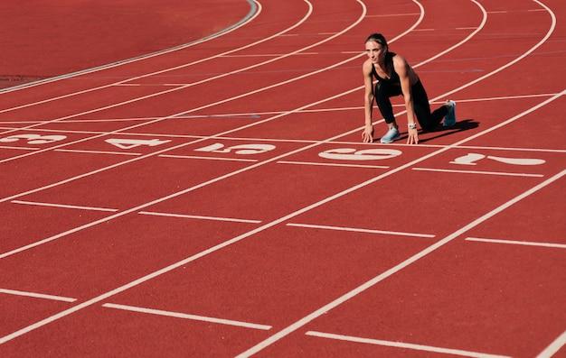 Mulher jovem corredor no sportwear, preparando-se para correr sprint no início baixo na pista do estádio com vermelho revestido em um dia ensolarado