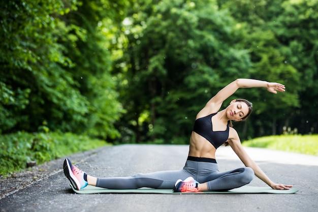 Mulher jovem corredora alongando as pernas antes de correr no parque da cidade