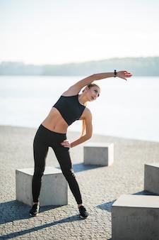 Mulher jovem corredora alongando as pernas antes de correr