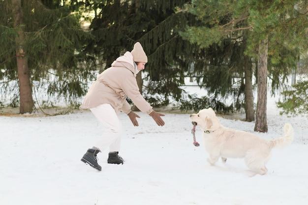 Mulher jovem correndo na neve junto com seu cachorro e brincando com um brinquedo do lado de fora