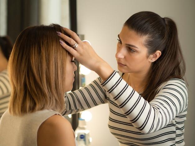 Mulher jovem corrigindo as sobrancelhas em um salão de beleza