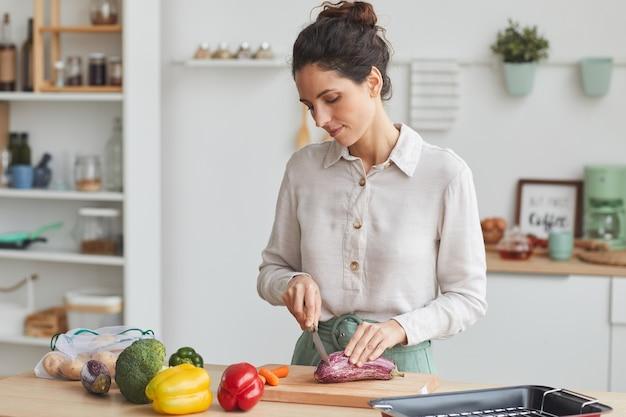 Mulher jovem cortando legumes frescos numa tábua ela preparando o jantar na cozinha
