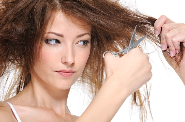 Mulher jovem cortando o cabelo castanho escuro, isolado no branco
