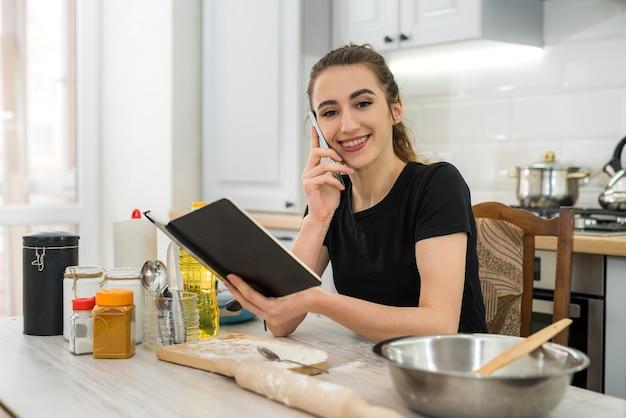 Mulher jovem cozinhando bolo com farinha lendo a receita do bloco de notas na mesa da cozinha