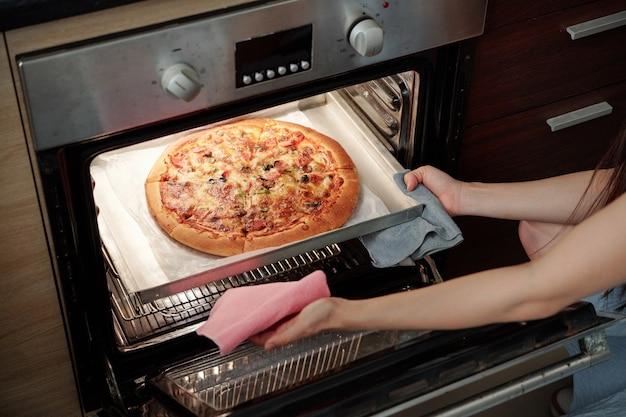 Mulher jovem cozinhando pizza