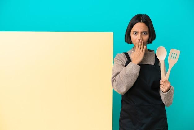Mulher jovem cozinheira de raça mista com um grande cartaz isolado em um fundo azul cobrindo a boca com a mão