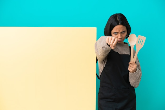 Mulher jovem cozinheira de raça mista com um grande cartaz isolado em um fundo azul com gesto de luta