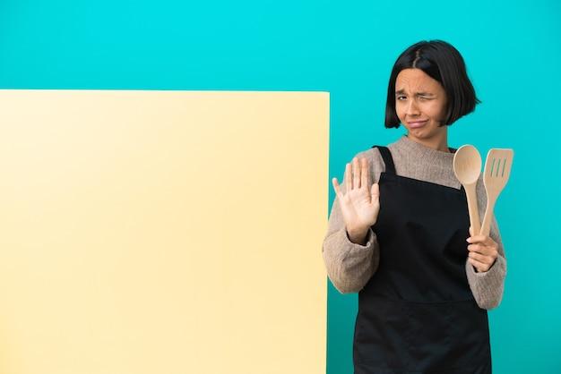 Mulher jovem cozinheira de raça mista com um grande cartaz isolado em um fundo azul nervosa esticando as mãos para a frente