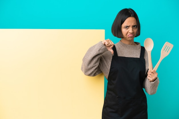 Mulher jovem cozinheira de raça mista com um grande cartaz isolado na parede azul, fazendo sinais de bom-mau. indeciso entre sim ou não