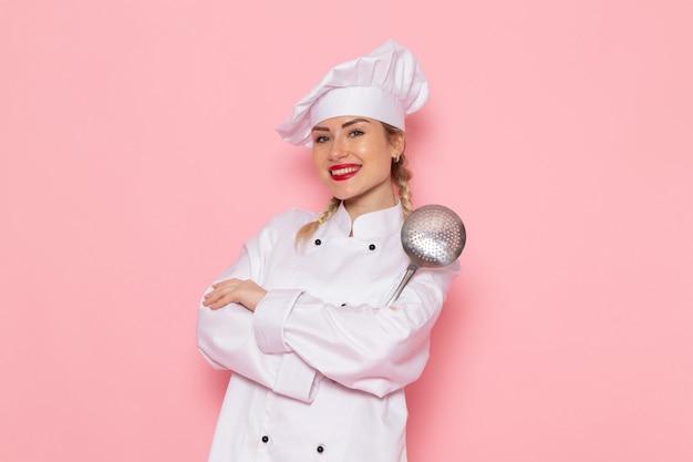 Mulher jovem cozinheira de terno branco posando com expressão encantada na foto rosa do cozinheiro espacial