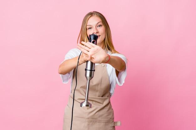 Mulher jovem cozinheira russa segurando uma batedeira isolada e fazendo um gesto de negação