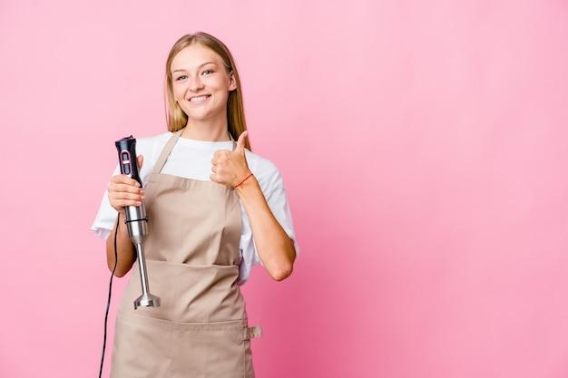 Mulher jovem cozinheira russa segurando uma batedeira isolada, sorrindo e levantando o polegar