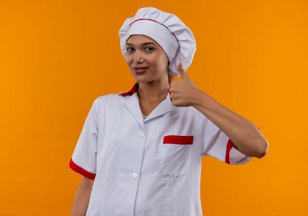 Mulher jovem cozinheira satisfeita usando uniforme de chef com o polegar para cima na parede laranja isolada