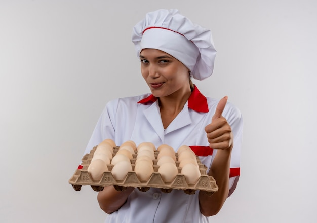 Mulher jovem cozinheira satisfeita vestindo uniforme de chef segurando lote de ovos com o polegar para cima na parede branca isolada