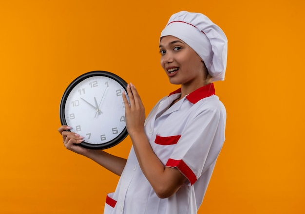 Mulher jovem cozinheira satisfeita vestindo uniforme de chef segurando um relógio de parede na parede laranja isolada com espaço de cópia