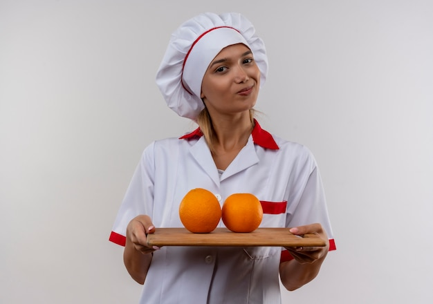 Mulher jovem cozinheira satisfeita vestindo uniforme de chef segurando uma laranja na tábua na parede branca isolada com espaço de cópia