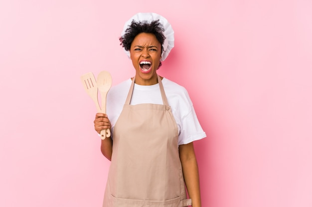 Mulher jovem cozinheiro americano africano gritando muito irritado e agressivo.