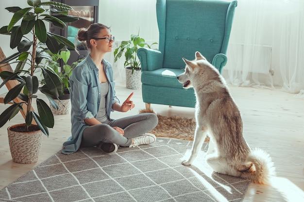 Mulher jovem criando e brincando com seu cachorro doméstico husky siberiano em casa