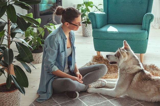 Mulher jovem criando e brincando com seu cachorro doméstico siberian h