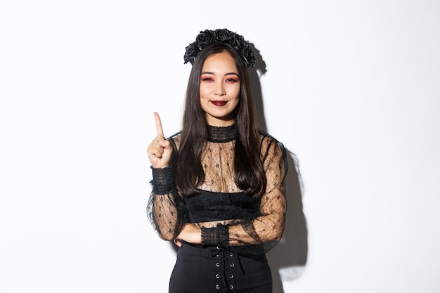Mulher jovem criativa fantasiada de bruxa, sorrindo satisfeito, pois tem uma ótima ideia, levantando o dedo para dizer sugestão. mulher asiática vestida como viúva ou mágico misterioso, fundo branco.