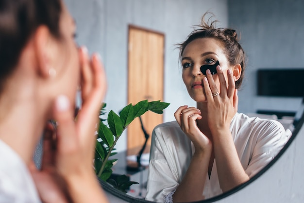 Mulher jovem cuida da pele do rosto em casa.