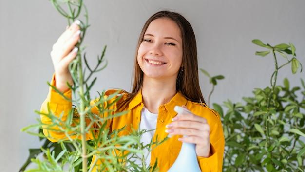 Mulher jovem cuidando de suas plantas em casa