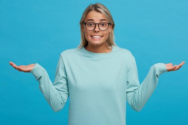 Mulher jovem culpada e confusa dando de ombros, fazendo um gesto desamparado com as mãos
