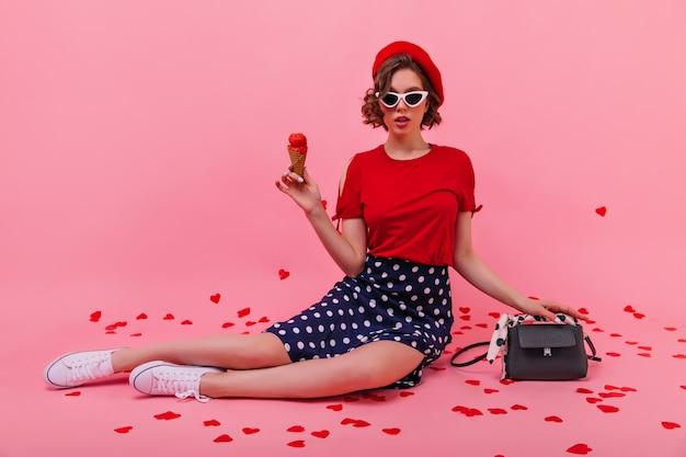 Mulher jovem curiosa em saia segurando sorvete. garota francesa confiante na boina comendo sobremesa.
