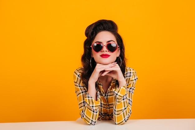 Mulher jovem curiosa sentada sobre fundo amarelo. foto de estúdio de linda garota pin-up usando óculos em forma de coração.