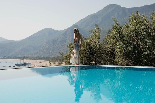 Mulher jovem curtindo as férias no topo de uma rocha com vista luxuosa, mostrando emoção no fundo do mar azul na piscina